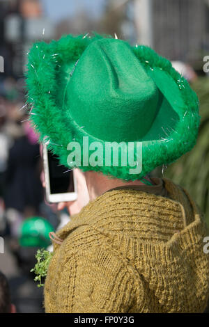 Belfast, Ireland 17th March. A man wearing a green Cowboy hat and Arran jumper and a sprig of Shamrock checks his - Stock Photo
