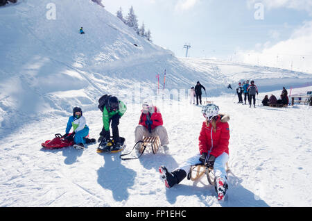 Teenagers and children sledging in the Swiss Alps at Lenk, Canton of Bern, Switzerland, Europe - Stock Photo