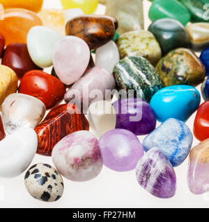 many tumbled natural mineral gemstones close up on white - Stock Photo