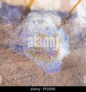 rainbow stain of motor oil on wet asphalt pavement in city - Stock Photo