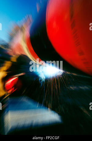 Abstract view of man welding a pipeline seam in rural West Virginia; USA - Stock Photo