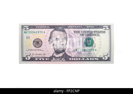 A single American Five Dollar note photographed against a white background - Stock Photo