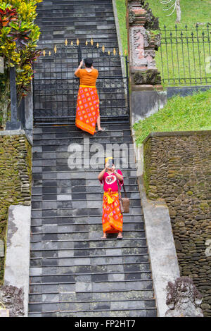Asia, Indonesia, Bali. Visitors at Pura Tirta Empul Temple taking 'selfies' photographs with their cell phones. - Stock Photo