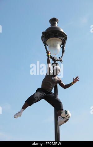 acrobatic performance artist at an old gas lamp on the hill of Sacre Coeur in Montmartre, Paris - Stock Photo
