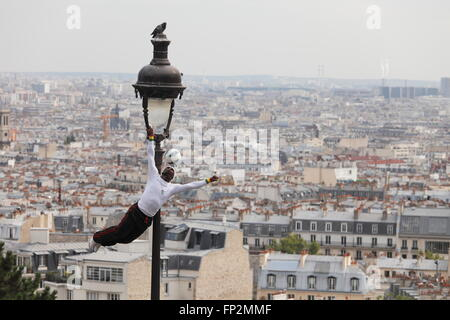 acrobatic performance artist at an old gas lamp on the hill of Sacre Coeur in Montmartre Paris, France - Stock Photo