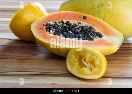 close up of a papaya cut in half on a wooden cutting board served with a sliced lemon - Stock Photo