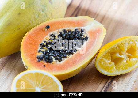 close up of a papaya cut in half on a wooden cutting board served with a sliced lemon
