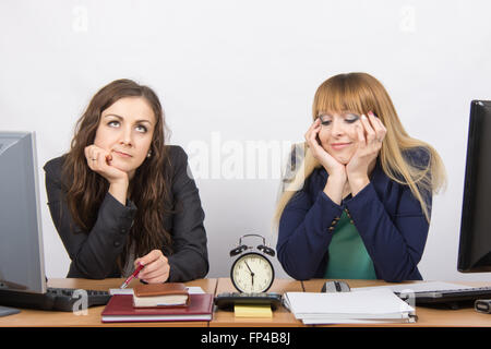 Two bored office worker waiting for the end of the day and look at the clock - Stock Photo