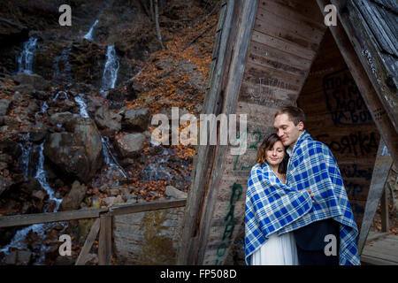 Happy wedding couple wrapped in blanket tenderly hugs with eyes closed. Wodden bridge at the mountains - Stock Photo