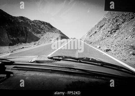 STRAIGHT ROAD AT A DRY AND DESERT LANDSCAPE SHOOT THROUGH A VERY OLD CARS WINDSCREEN GLASS IN BLACK AND WHITE, EGYPT - Stock Photo
