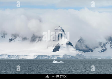 Calving glacier and clouds covering the coastline of Paradise Bay, Antarctic Peninsula. Paradise Harbor, also known - Stock Photo