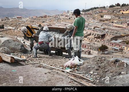 Miners emptying mine cart at Cerro Rico silver mine, Potosi. El Cerro Rico which translates ' the rich hill'  stands - Stock Photo