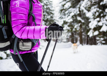 Winter trek in white woods. Woman hiking trekking in winter forest with dog. Travel recreation fitness and healthy - Stock Photo