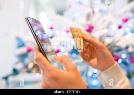 Woman using mobile phone and credit card. Shopping online. Christmas tree boke background - Stock Photo