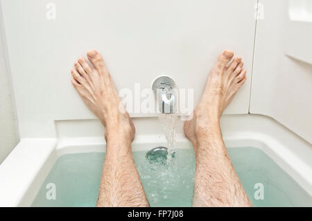 Bathtub With Water Running And Man's Feet - Stock Photo