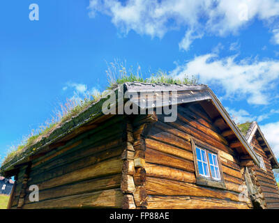 Typical small log house with grass roof in Norway - Stock Photo