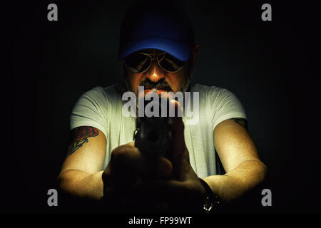 Facial expression of a man with tattoo and gun. - Stock Photo