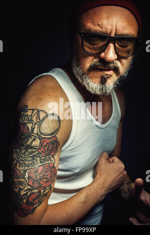 Portrait of an older man showing his tattoo. - Stock Photo