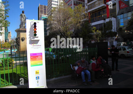 La Paz, Bolivia, 18th March 2016. People sit in the shade next to a radiation meter showing red / high solar UV - Stock Photo