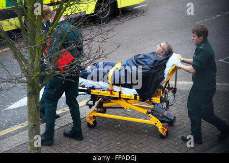 Paramedics wheeling patient on a stretcher into an ambulance in a residential area of North London - Stock Photo