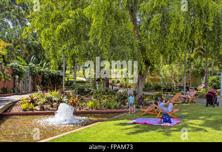 Families relaxing  on lawn / gardens in deck chairs around fountain, pond, and willow trees in roma street parklands - Stock Photo