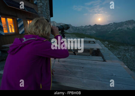 A woman looks at the full moon over Prättigau mountains with a telescope on the Carschina mountain hut in the Swiss - Stock Photo
