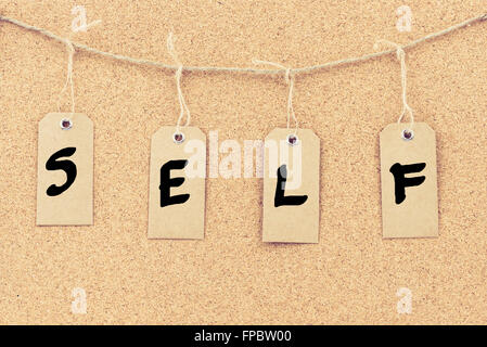 vintage grunge tags with letters on rope string word self over cork board texture background