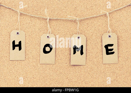 vintage grunge tags with letters on rope string word home over cork board texture background