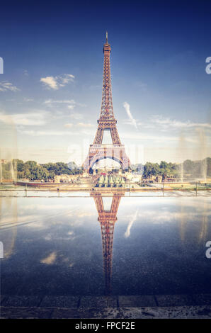 Toned enhanced scenic view of the Eiffel Tower, Paris, France reflected in still water with the fountains and park - Stock Photo