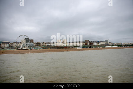 View of the waterfront and beach at Brighton showing the ferris wheel and architecture of the buildings on a grey - Stock Photo