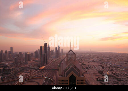 A sunset over Dubai. Showing the city with the skyscrapers in view. - Stock Photo