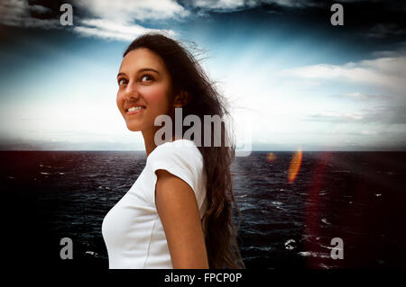 Smiling attractive young Indian woman standing looking up into the air with a dreamy expression against a dark dramatic - Stock Photo