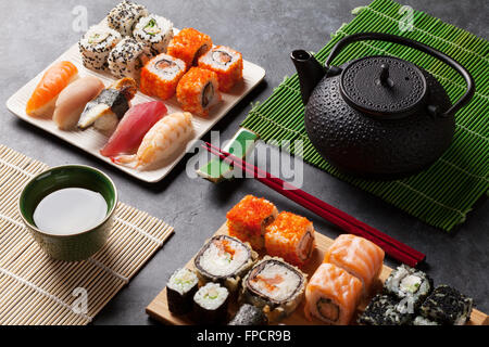 Set of sushi and maki roll and green tea on stone table - Stock Photo