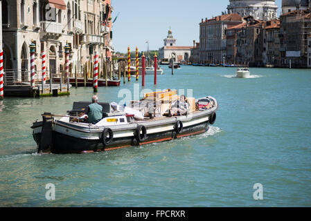Barge with two men traveling on the Grand Canal at the Academia bridge in Venice on a sunny spring day - Stock Photo