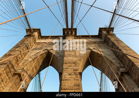 Structural detail of Brooklyn Bridge, New York, looking up one of the central stone support towers at the suspension - Stock Photo