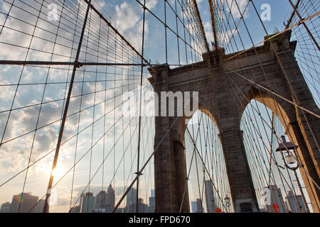 Detail of the suspension cables, Brooklyn Bridge looking up near one of the towers towards a sunset in cloudy sky - Stock Photo