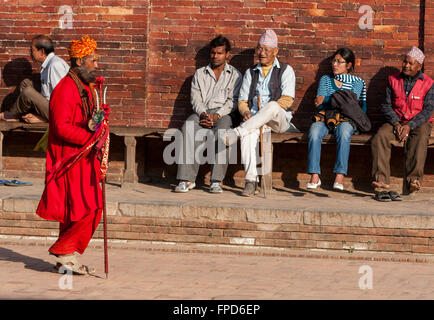 Nepal, Patan.  A Hindu Sadhu (Holy Man) Walks Past Men and One Woman Resting on Bench in Durbar Square. - Stock Photo