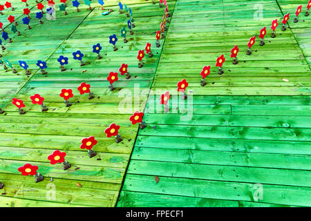 Artistic wooden garden with colorful red and blue flowers in concentric circles on a bright green wooden deck, copyspace - Stock Photo