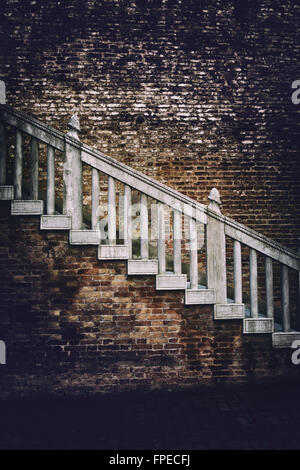 Old external staircase on a red brick building with heavy vignetting around the sides and an ominous ambiance, highlight - Stock Photo