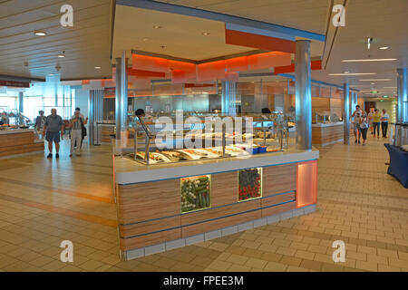 Cruise ship liner early morning interior on large cafeteria deck with breakfast buffet style self service food counters - Stock Photo