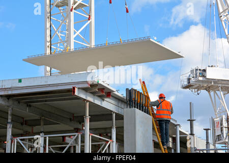 Construction site worker on ladder as crane positions large precast concrete floor panel on new apartment block - Stock Photo