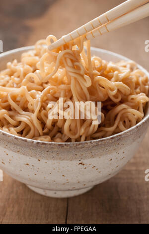 Ramen noodles in a traditional ceramic bowl with chopsticks - Stock Photo