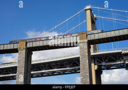 Train crossing the Royal Albert Bridge over the river Tamar above Saltash with the Tamar road bridge in the background. - Stock Photo