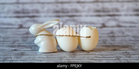 Small Ceramic Easter Bunny Pulling Broken Egg Shells Using Small Rope on Top of a Wooden Table in a Fuzzy Background. - Stock Photo