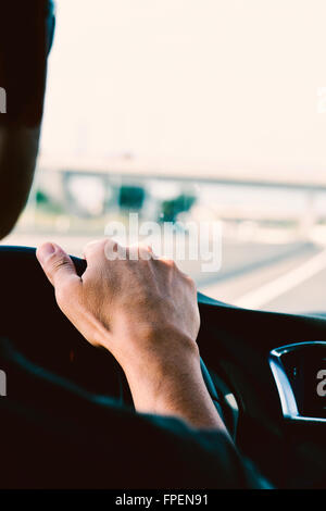 closeup of a young caucasian man, seen from behind, driving a car in a road with several lanes - Stock Photo