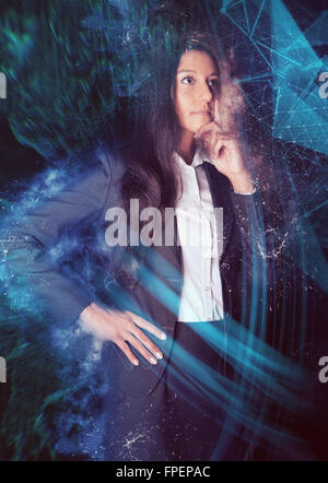 Three Quarter Length Portrait of Thoughtful Young Business woman Wearing Suit Standing with Hand on Chin in front - Stock Photo