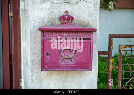 Vintage faded red post box mounted on a white wall in Germany showing the old post horns in raised relief - Stock Photo