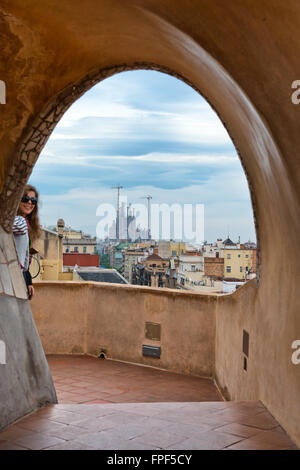 Antoni Gaudi Architecture - View of Sagrada Familia Church in Distance Under Storm Clouds as seen Through Arch on - Stock Photo