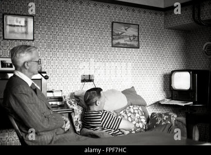 1950s historical, father and son in the front room watching television. - Stock Photo