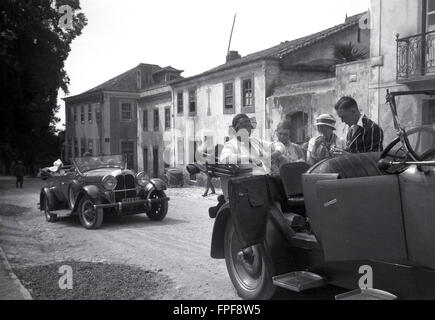 1930s historical, people on a Grand Tour of Europe in an open topped car enjoying a cigarette. - Stock Photo